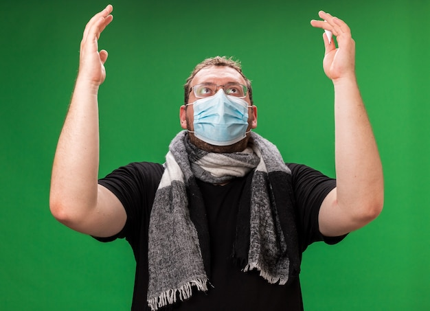 Zieke man van middelbare leeftijd opzoeken met een medisch masker en een sjaal die handen opsteekt