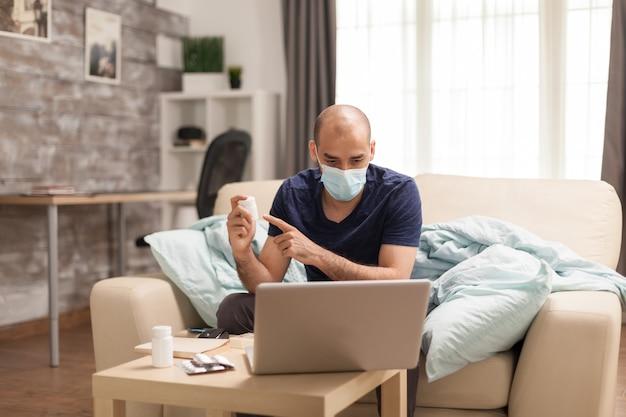 Zieke man wijzend op pillenfles tijdens online overleg met zijn arts.