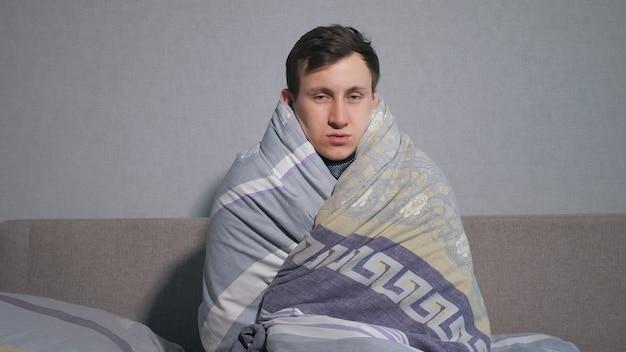 Zieke man wikkelt zich in een warme deken en rilt van de kou.