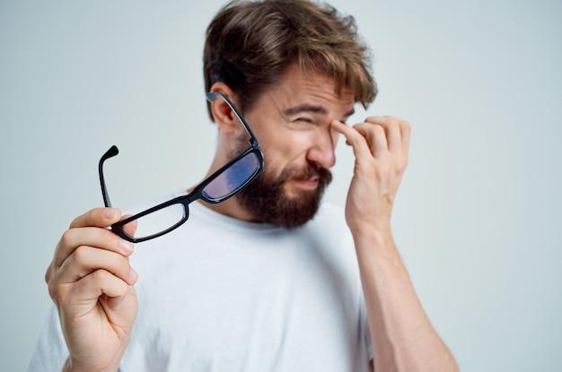 Zieke man zichtproblemen in wit t-shirt close-up. hoge kwaliteit foto