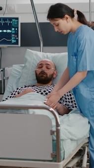 Zieke man zit in bed met een zuurstofslang die het ziektesymptoom uitlegt aan de beoefenaar, terwijl hij een ziektebehandeling op het klembord schrijft. medisch verpleegkundige die oximeter zet die herstel onderzoekt