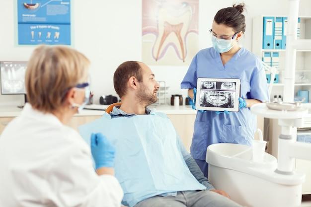 Zieke man zit op een tandartsstoel en kijkt naar radiografie op digitale tablet