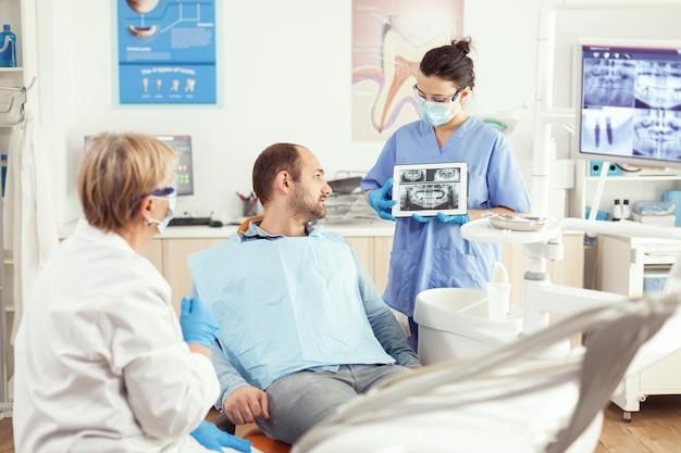 Zieke man zittend op stomatologische stoel luisterende arts terwijl hij naar tablet kijkt in de tandheelkundige kliniek