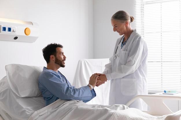 Zieke mannelijke patiënt in bed in gesprek met een verpleegster