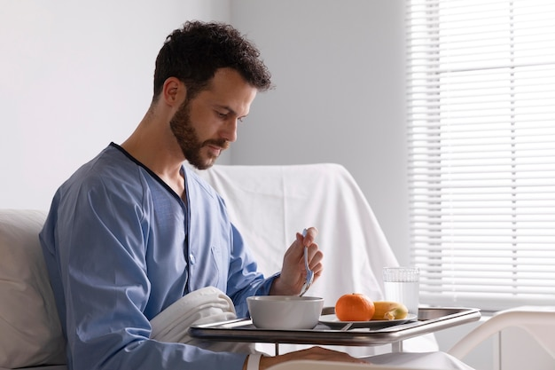 Zieke mannelijke patiënt in bed in het ziekenhuis