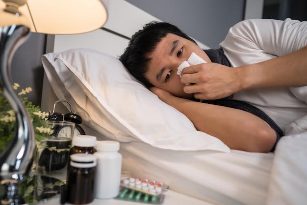 Zieke mens die in weefsel niest dat in bed ligt