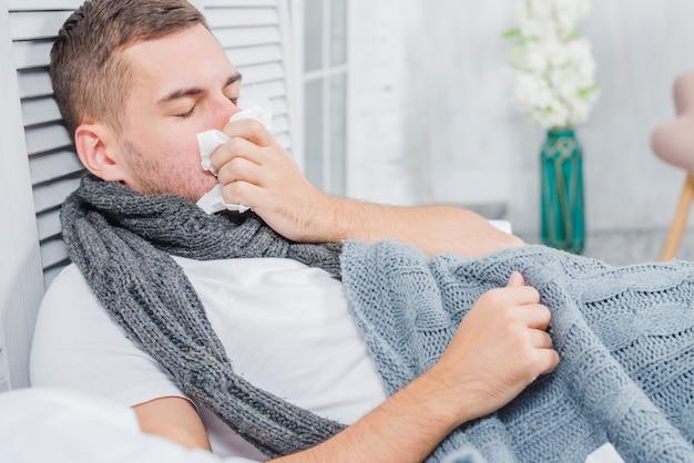 Zieke mens die zijn neus met wit papieren zakdoekje blaast dat op bed ligt