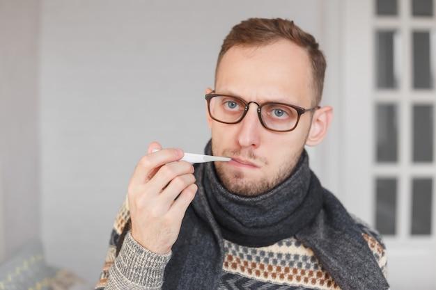 Zieke mens die zijn temperatuur thuis in de woonkamer controleert. man in sjaal houdt thermometer in mond. meet temperatuur
