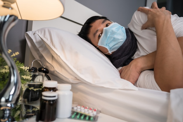 Zieke mens in medisch masker die koud voelen en aan virusziekte en koorts in bed lijden, coronavirus pandemisch concept.