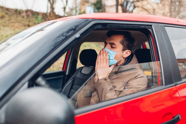 Zieke mensenzitting in auto die beschermend masker draagt dat hoest hebbend griepcoronavirus. verbod op autorijden met koorts.