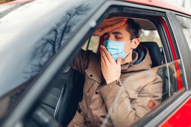 Zieke mensenzitting in auto die beschermend masker draagt dat ziek voelt hebbend griepcoronavirus. verbod op autorijden met koorts.