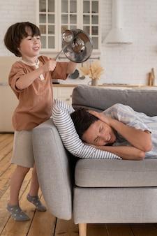 Zieke moeder liggend op de bank lijdt aan hoofdpijn of migraine klein ondeugend zoon kind maakt geluiden in de buurt