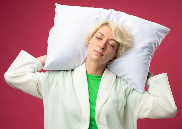 Zieke ongezonde vrouw met het kussen van de kort haarholding met gesloten ogen die zich over roze achtergrond bevinden