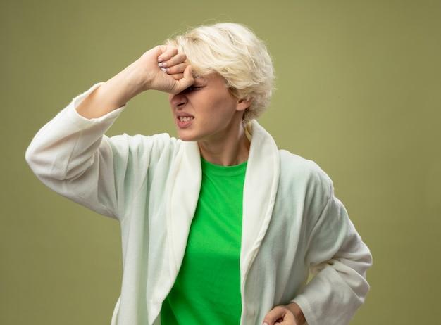 Zieke ongezonde vrouw met kort haar die zich onwel voelen wordt boos aanraken van haar voorhoofd staande over lichte achtergrond
