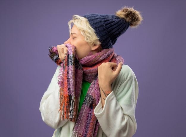 Zieke ongezonde vrouw met kort haar in warme muts en sjaal die zich onwel voelen hoesten over paarse muur