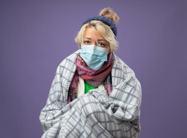 Zieke ongezonde vrouw met kort haar in warme muts en sjaal dragen beschermende gezichtsmasker gewikkeld in deken onwel gevoel camera ongelukkig kijken over paarse achtergrond