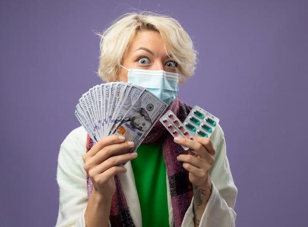 Zieke ongezonde vrouw met kort haar in warme sjaal en beschermend gezichtsmasker met contant geld en blister met pillen bezorgd en verward staande over paarse muur