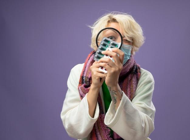 Zieke ongezonde vrouw met kort haar in warme sjaal en beschermend gezichtsmasker pillen kijken door vergrootglas staande over paarse muur