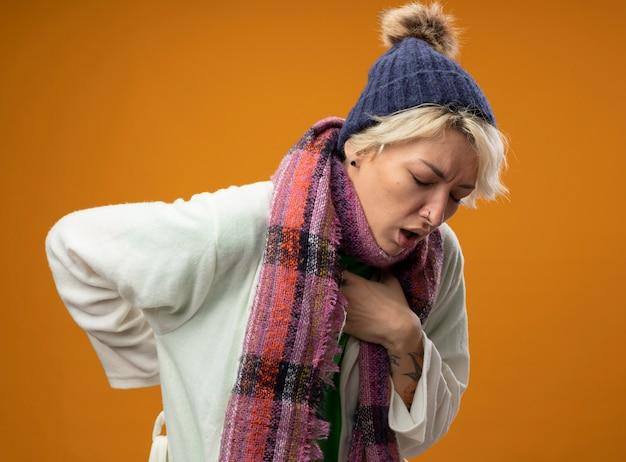 Zieke ongezonde vrouw met kort haar in warme sjaal en dat gevoel onwel hoesten lijden aan koude staande over oranje achtergrond