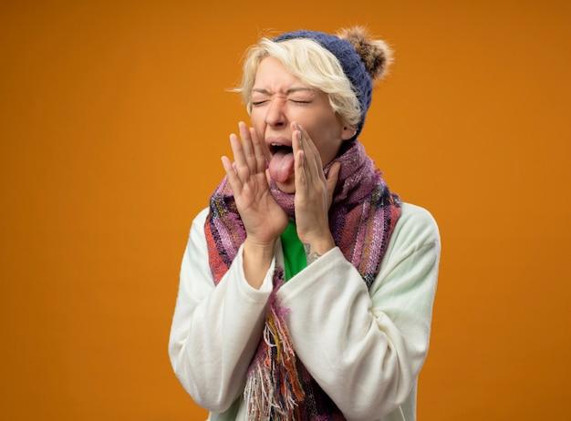 Zieke ongezonde vrouw met kort haar in warme sjaal en dat gevoel onwel hoesten tong uitsteekt staande over oranje achtergrond