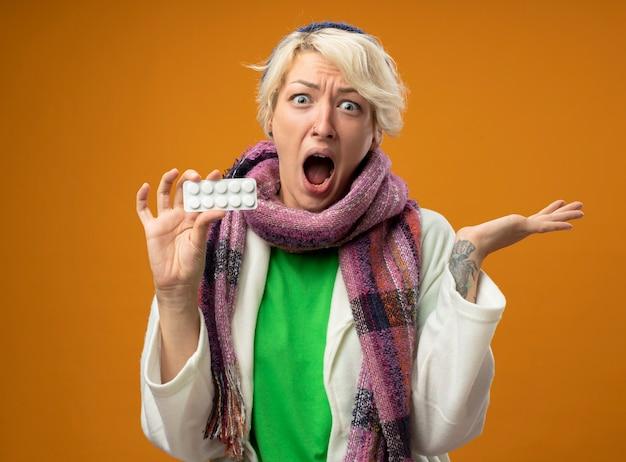 Zieke ongezonde vrouw met kort haar in warme sjaal en hoed die pillen toont die verward en teleurgesteld over oranje muur kijken