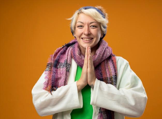 Zieke ongezonde vrouw met kort haar in warme sjaal en muts die hand bij elkaar houdt als bidden, zich beter voelen glimlachend over oranje muur staan