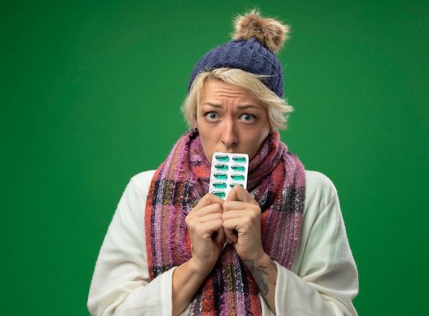 Zieke, ongezonde vrouw met kort haar in warme sjaal en muts die zich onwel voelen en blaren vasthouden met pillen die van streek zijn en ongelukkig over groene muur staan