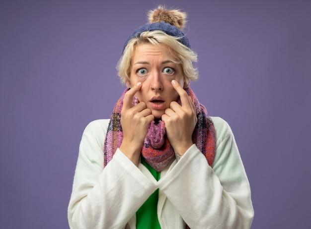Zieke ongezonde vrouw met kort haar in warme sjaal en muts die zich onwel voelen kijken naar camera wijzend met index figner naar haar ogen verrast over paarse achtergrond