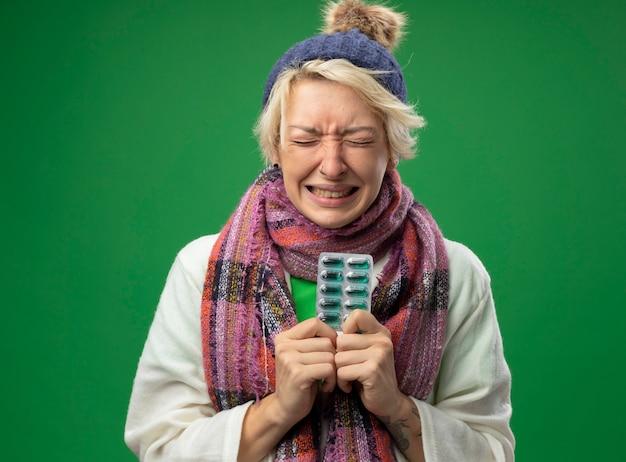 Zieke ongezonde vrouw met kort haar in warme sjaal en muts die zich onwel voelt met blisterverpakking met pillen met geïrriteerde uitdrukking op gezicht staande over groene achtergrond