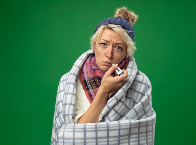 Zieke ongezonde vrouw met kort haar in warme sjaal en muts gevoel onwel gewikkeld in een deken met thermometer in haar mond staande over groene achtergrond