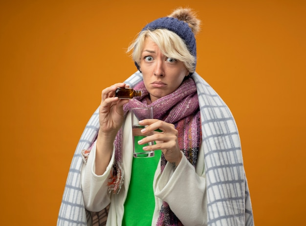 Zieke ongezonde vrouw met kort haar in warme sjaal en muts gewikkeld in deken druipende geneeskunde druppels in een glas camera kijken verward staande over oranje achtergrond