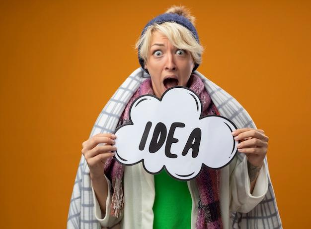 Zieke ongezonde vrouw met kort haar in warme sjaal en muts gewikkeld in een deken houden toespraak bubble bord met woord idee camera kijken verbaasd en verbaasd staande over oranje achtergrond