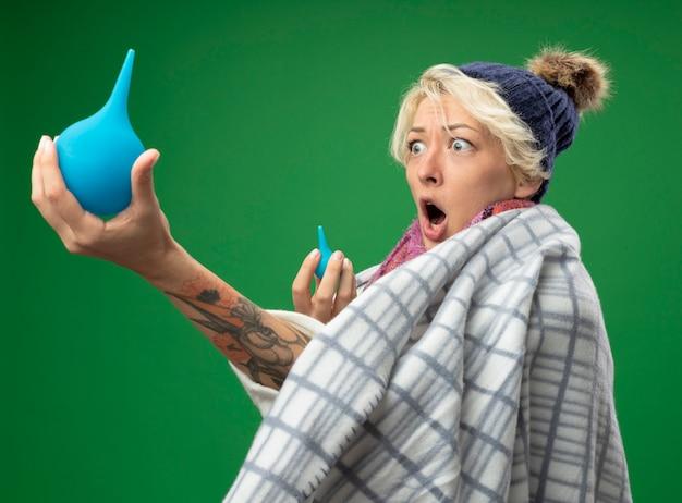 Zieke ongezonde vrouw met kort haar in warme sjaal en muts gewikkeld in een deken met klysma kijken verbaasd over groene muur staan