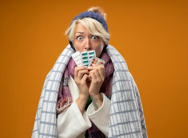 Zieke ongezonde vrouw met kort haar in warme sjaal en muts gewikkeld in een deken met pillen bezorgd staande over oranje muur