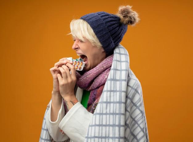 Zieke ongezonde vrouw met kort haar in warme sjaal en muts gewikkeld in een deken met pillen die ze allemaal in de mond houden over oranje muur