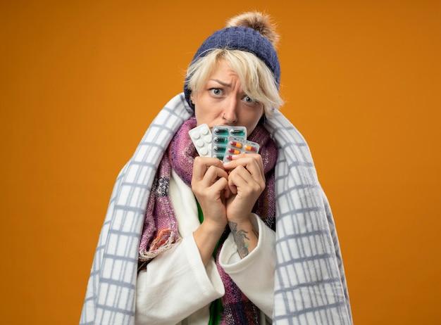 Zieke ongezonde vrouw met kort haar in warme sjaal en muts gewikkeld in een deken met pillen met droevige uitdrukking staande over oranje muur