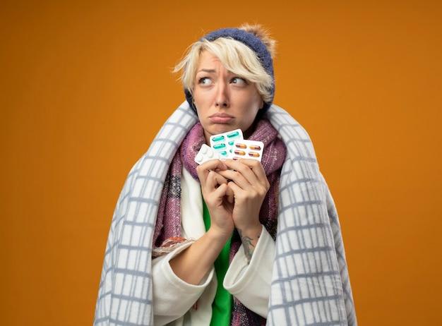 Zieke ongezonde vrouw met kort haar in warme sjaal en muts gewikkeld in een deken met pillen opzij kijken met hoop expressie staande over oranje muur