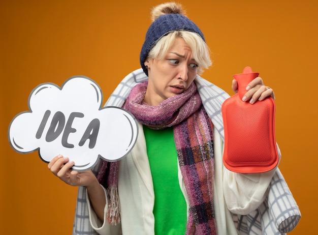 Zieke ongezonde vrouw met kort haar in warme sjaal en muts gewikkeld in een deken met waterfles om warm te houden en toespraak bubble bord met woord idee op zoek verward en bezorgd