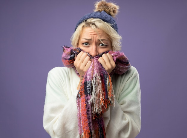 Zieke ongezonde vrouw met kort haar in warme sjaal en muts maakte zich zorgen over de paarse muur en was nerveus