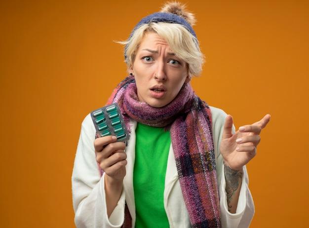 Zieke ongezonde vrouw met kort haar in warme sjaal en muts met blister met pillen wijzen met wijsvinger naar de zijkant op zoek verward staande over oranje muur