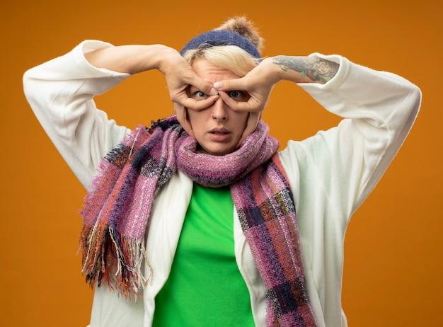 Zieke ongezonde vrouw met kort haar in warme sjaal en muts verrekijker gebaar maken met vingers permanent over oranje muur