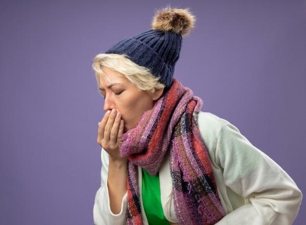 Zieke ongezonde vrouw met kort haar in warme sjaal en muts zich onwel voelen hoesten lijdt aan griep staande over paarse muur