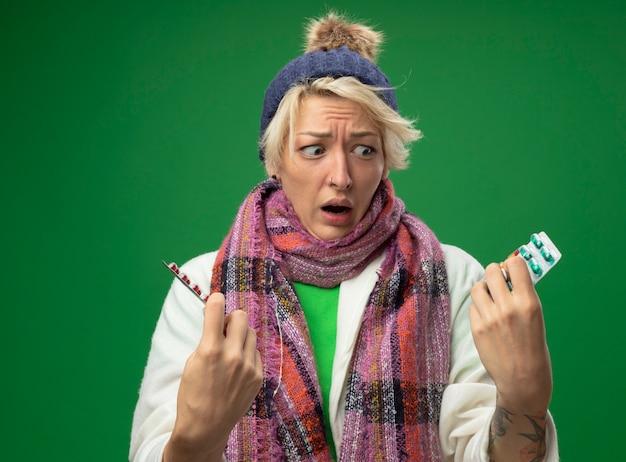 Zieke ongezonde vrouw met kort haar in warme sjaal en muts zich onwel voelen met blaren met pillen kijken camera bezorgd en verward proberen te maken keuze staande op groene achtergrond