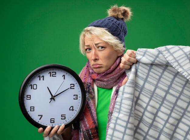 Zieke ongezonde vrouw met kort haar in warme sjaal en muts zich onwel voelen verpakt in een deken houden wandklok lookign camera met ernstige faceover groene achtergrond
