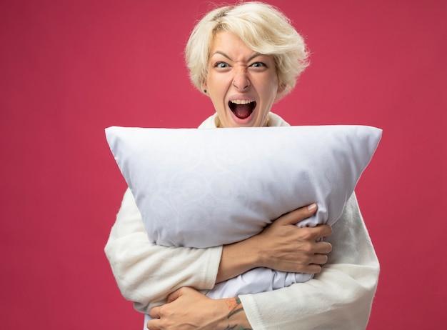 Zieke ongezonde vrouw met kort haar knuffelen kussen camera kijken schreeuwen met agressieve uitdrukking staande over roze achtergrond