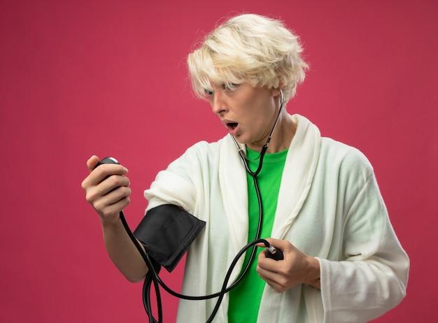 Zieke ongezonde vrouw met kort haar met een stethoscoop die haar bloeddruk meet streesed en nerveus staande over roze achtergrond