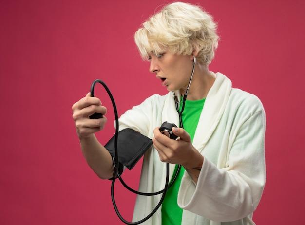 Zieke ongezonde vrouw met kort hairwith stethoscoop die haar bloeddruk meet die verward status over roze achtergrond kijkt