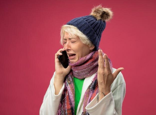 Zieke, ongezonde vrouw van streek met kort haar in warme sjaal en hoed, zich onwel voelen, huilen tijdens het praten op mobiele telefoon met opgeheven arm staande over roze muur