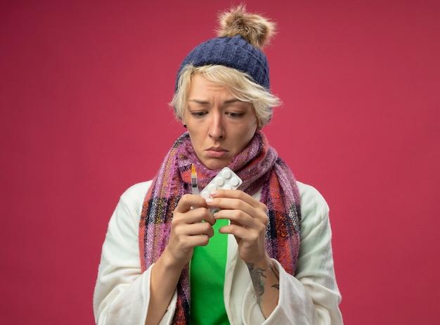 Zieke, ongezonde vrouw van streek met kort haar in warme sjaal en muts, zich onwel voelen met medicijnen en spuit op zoek verward en erg angstig staande over roze achtergrond