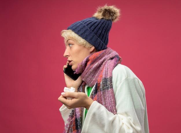 Zieke, ongezonde vrouw van streek met kort haar in warme sjaal en muts, zich onwel voelen met papieren servet terwijl ze over de roze muur praat op mobiele telefoon